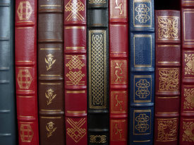 image of leather-bound  - a row of leather bound books on a shelf - JPG