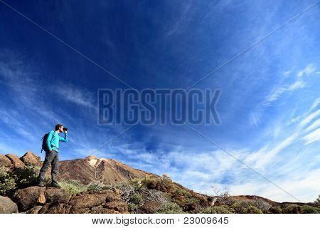 hiker in dramatic landscape hiking under deep blue sky looking in binoculars. Young Caucasian man during hike in Mountain landscape on volcano Teide, Tenerife, Canary Islands
