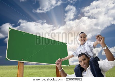 Attractive Happy Hispanic Father and Son in Front of Blank Green Road Sign Ready for Your Own Message.