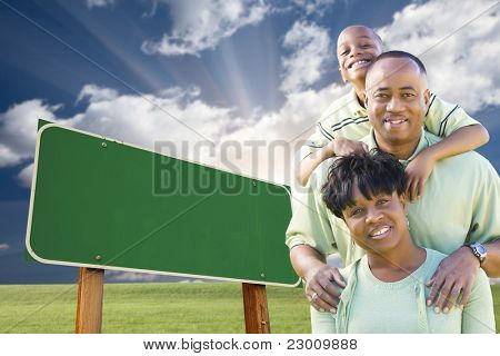 Attractive African American Family in Front of Blank Green Road Sign Ready for Your Own Message.