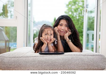 Portrait of mother and daughter lying on couch with digital tablet