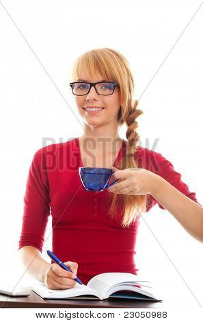 Young Woman Student At Table With Notebook And Cup