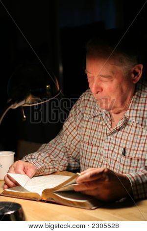 Homem idoso lendo sua Bíblia sob Lamplight.