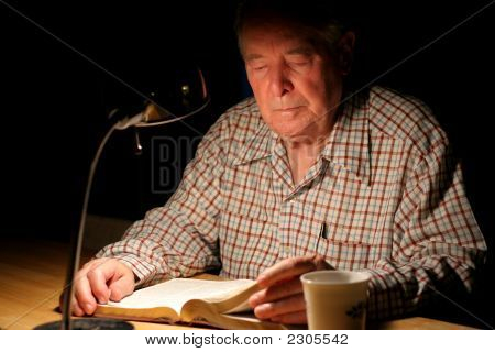 Elderly Man Reading His Bible Under Lamplight