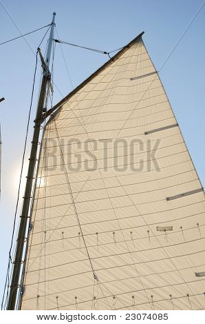 Mainsail And Wooden Mast Of Schooner Sailboat