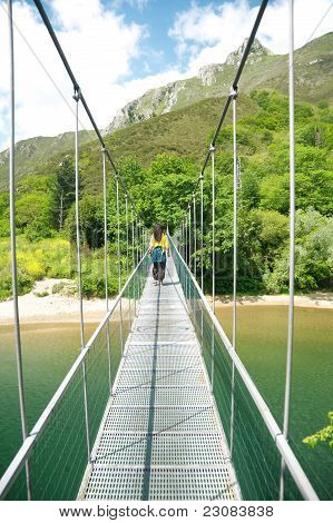 Walking On Footbridge Over River
