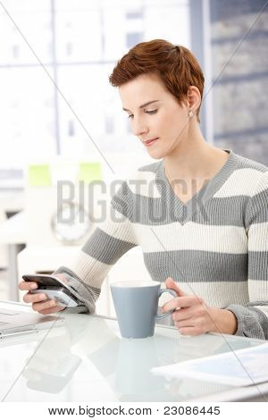 Office worker girl sitting at desk, using smartphone, having coffee.?