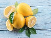 Ripe lemons and lemon leaves on blue wooden background. Top view. poster