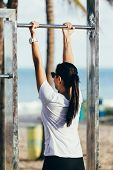 Fitness Woman Exercising On Chin-up Bar. Lady Doing Chin-ups Outside On Beach In Summer poster