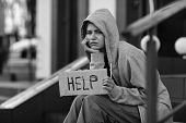 Homeless poor woman holding piece of cardboard with word HELP outdoors poster