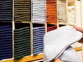 Women Hand Pick The Light Blue Sock From Socks Stack On Shelves For Sale In Clothing Store poster