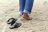Man Wearing Blue Jeans Leaving His Sandals Walking Bare Feet Casually Relax On A Sandy Beach poster