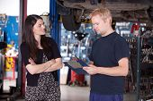 image of angry  - An angry customer talking to a mechanic in an auto repair shop - JPG