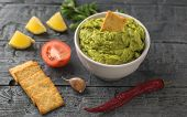 White Bowl With Fresh Guacamole, Tomatoes, Lemon, Chips And Garlic On Wooden Table. Diet Vegetarian  poster