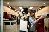 Technological Concept. Two Women In Modern Virtual Reality Headsets Having Expirience In Shopping At poster