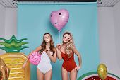 Perfect In Every Way.  Two Playful Young Women In Swimwear Looking At Camera And Smiling While Stand poster