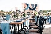 Wedding Catered Event Setting, Flowers, Candles, White Plates, Blue Napkins, Wooden Tables, Event De poster