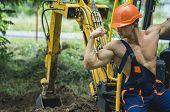 Sexy Builder Concept. Handsome Man Or Bodybuilder Wears Overalls. Muscular Builder In Hard Hat Shows poster