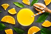 Orange Juice In Glass And Fresh Citrus Around On Black Stone Table. Fresh Orange Juice. Top View. poster