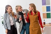 Happy Multiethnic Magazine Editors Celebrating With Champagne In Modern Office poster
