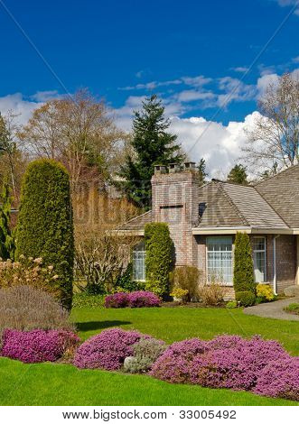 Manicured House and Garden displaying annual and perennial gardens in full bloom.