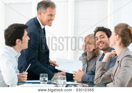 Mature business man working in team with his colleagues at office