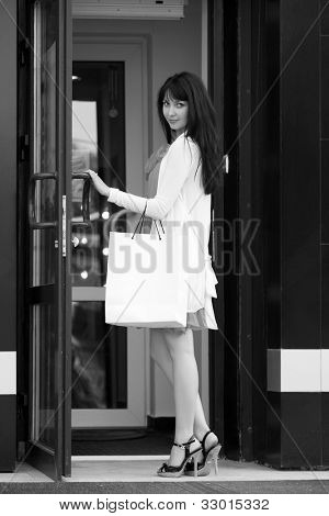 Young female shopper in a mall doorway