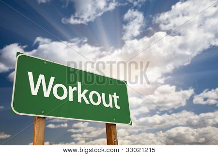 Workout Green Road Sign with Dramatic Clouds, Sun Rays and Sky.