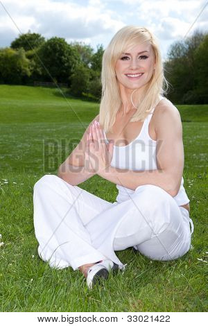 Smiling beautiful young blonde woman sitting cross-legged on green grass with her hands clasped in a yoga pose