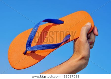 someone holding an orange flip-flops over the blue sky