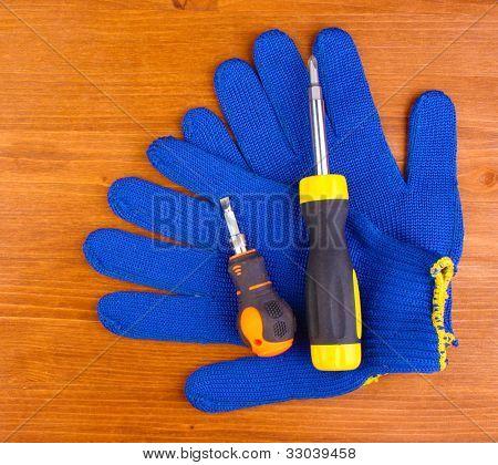Schraubendreher und Handschuhe auf hölzernen Hintergrund