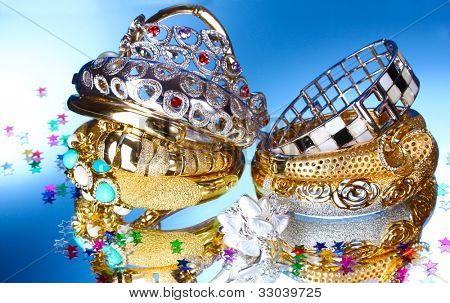 Beautiful silver and gold bracelets and ring on blue background