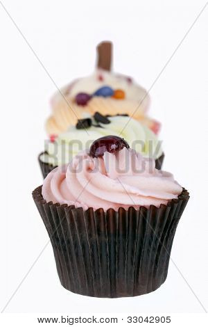 Row of cupcakes isolated on white background. Intentional shallow depth of field.