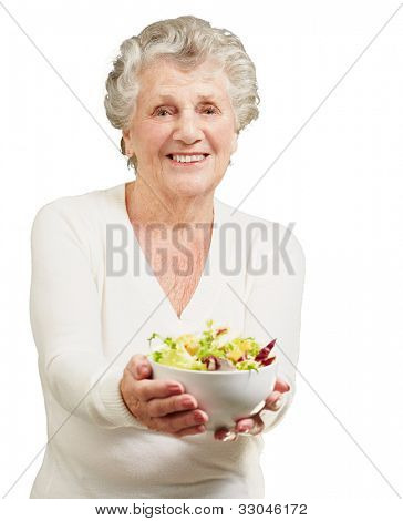 portrait of a senior woman showing a fresh salad over a white background