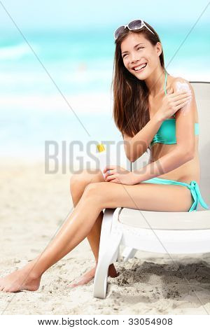 Suntan lotion - woman applying sunscreen smiling happy in bikini on beautiful beach on summer vacation on holiday resort. Pretty mixed race Asian Chinese / Caucasian female model in bikini on sunbed.