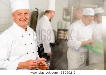 Professional kitchen smiling chef cook add spice paprika prepare food meals