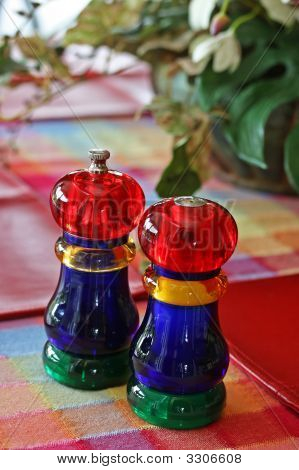 Colorful salt and pepper shakers on plaid table cloth Colorful salt and pepper shakers