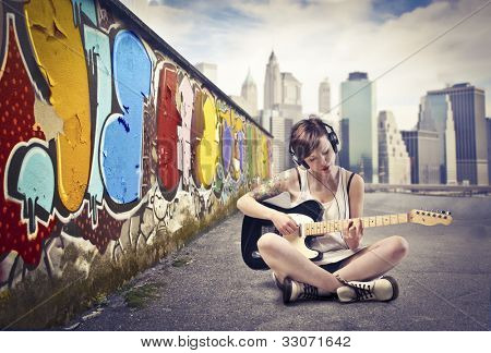 Beautiful young woman sitting on a city street and playing the electric guitar