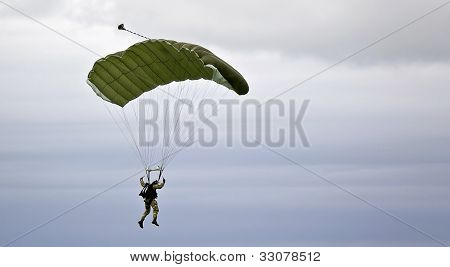 Military Parachutist On The Background Of Dark Sky