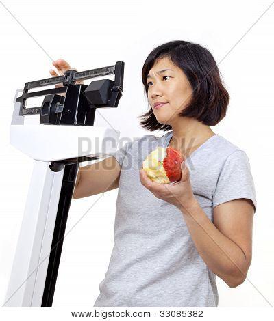 Frau mit Apfel im Maßstab Gewicht besorgt