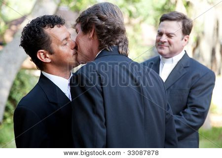 Wedding of handsome gay male couple.  The grooms kiss as the minister looks on.