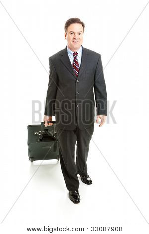 Full body isolated view of a business traveler carrying his rolling suitcase.