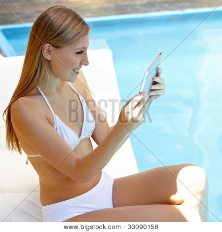 Attractive smiling woman reading Ebook on tablet computer near the swimming pool