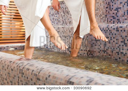 Man and woman while wellness water treading or hydrotherapy, only feet to be seen