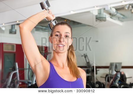 Young woman is exercising with barbell in gym to strengthen the muscles