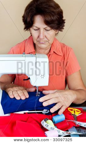 Hispanic woman working on a sewing machine with fabric and accessories on a table