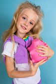 Fashion Girl Blonde With Long Hair In Sports Shirt, Shorts, Sneakers Standing And Holds A Pig Moneyb poster