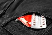 Red Condom And Birth Control Pills In Pocket Of Jeans, Closeup. Safe Sex Concept poster
