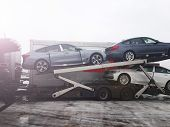 Loading New Cars From Conveyor Of Automobile Plant On The Truck For Delivery To Customers. Winter Su poster