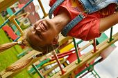 Child Girl Hanging Upside Down On The Playground. Smiling Teenager Girl Playing At A Sports Construc poster